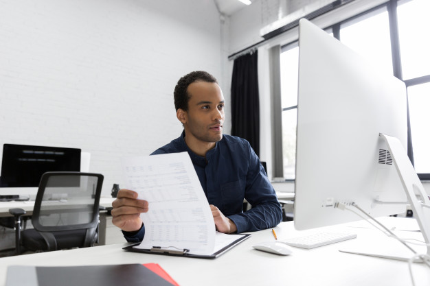 young-african-business-man-sitting-his-desk_171337-8324